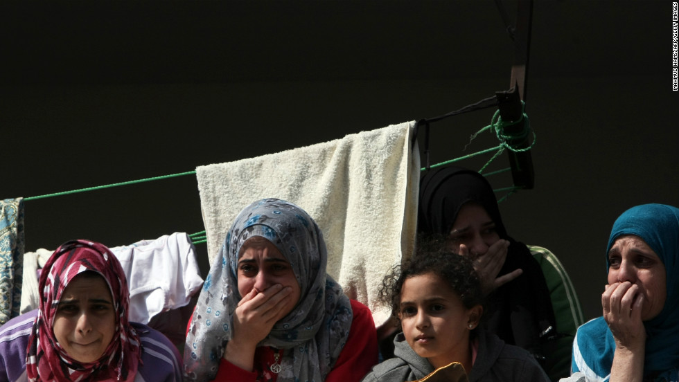 Palestinian women mourn during the funeral Monday of members of one family killed when an Israeli missile struck a three-story building in Gaza City on Sunday.