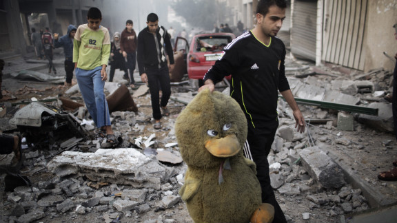 A Palestinian man carries a stuffed toy through a street littered with debris after an air raid on a sporting center in Gaza City on