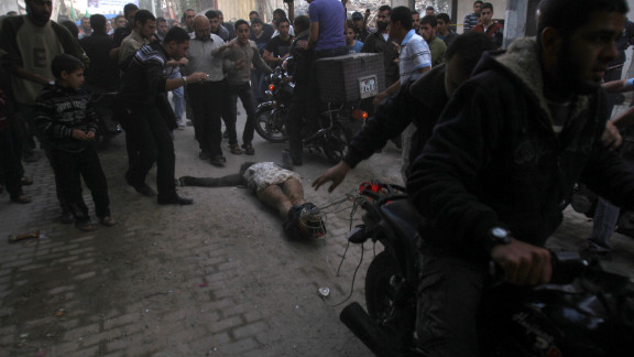 Men on motorcycles drag the body of man through the streets of Gaza City on Tuesday. The men dragging the body claimed it was the body of a collaborator and an Israeli spy.