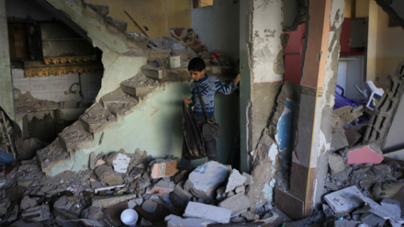 A Palestinian boy walks through the rubble of Hamas commander