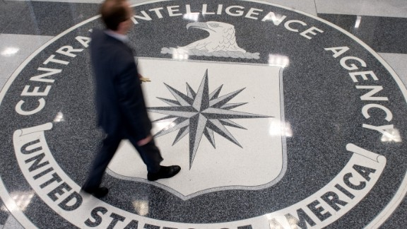 A man crosses the CIA logo in the lobby of the agency