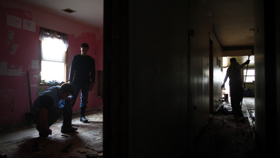 Volunteers on Tuesday remove flooring from a Keansburg, New Jersey, home damaged by the storm.