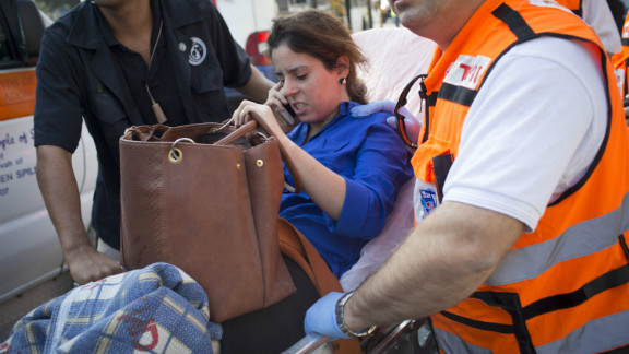 An injured woman is helped from the scene after the explosion.