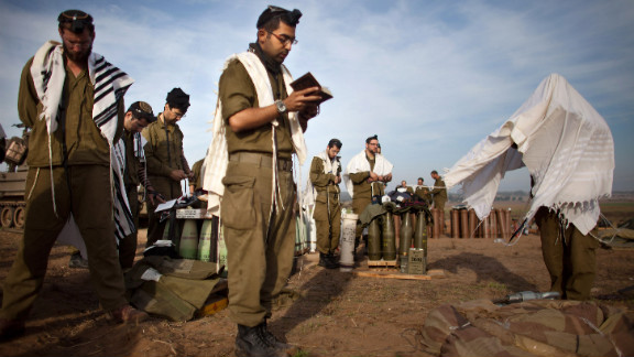 Israeli soldiers pray next to an artillery gun along Israel