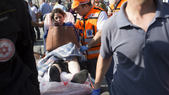 A woman is helped at the scene by emergency workers Wednesday after the explosion on the bus in Tel Aviv.