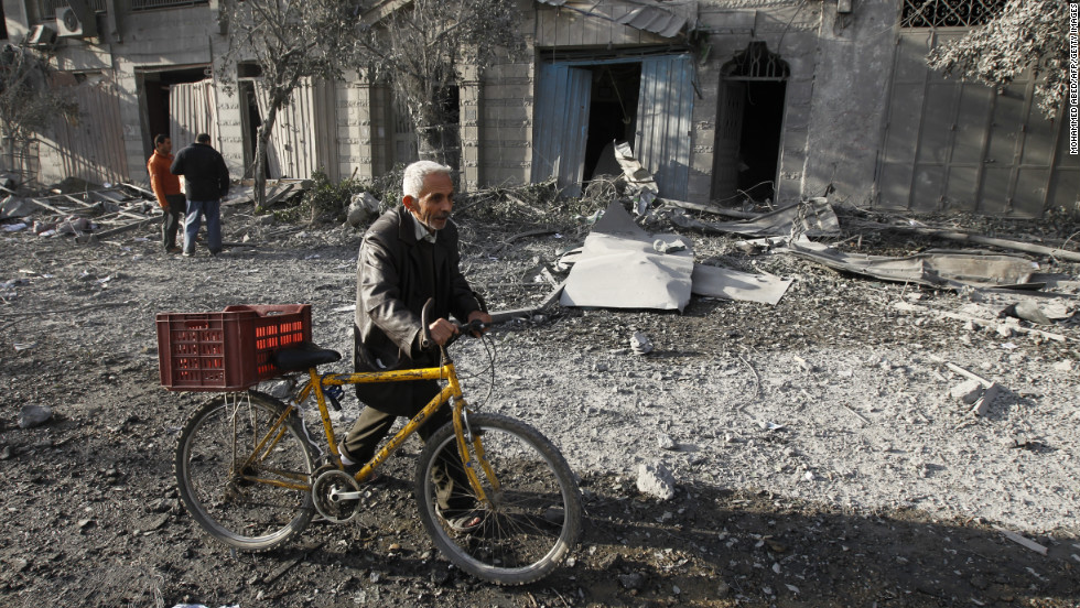 A Palestinian pushes his bicycle amid debris Wednesday near the destroyed compound of the Ministry of Internal Security in Gaza City. An Israeli airstrike targeted the building overnight.
