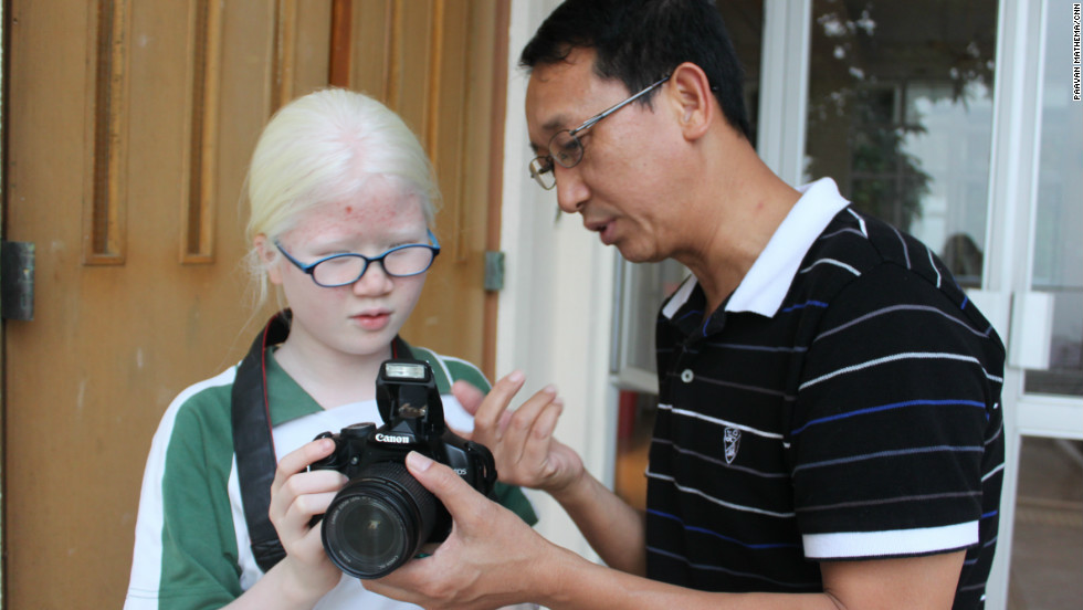 Ben Fong, a photography instructor at Ebenezer School, guides his student Eli Tang.