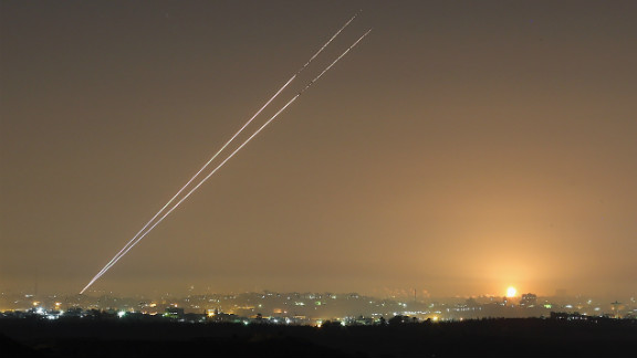 Rockets launch from Gaza City as an explosion is seen on the horizon at Israel