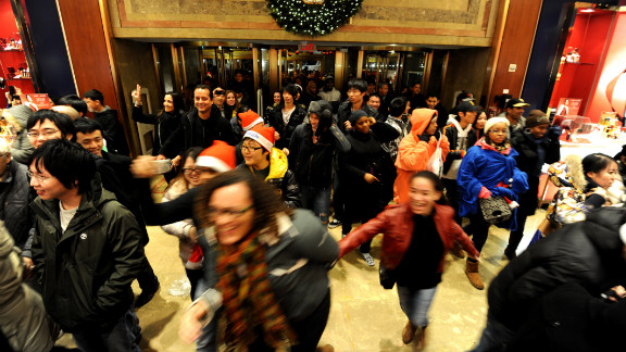 Black Friday shoppers gleefully rush through the doors of the New York City Macy's after it opened its doors at midnight on November 25, 2011.