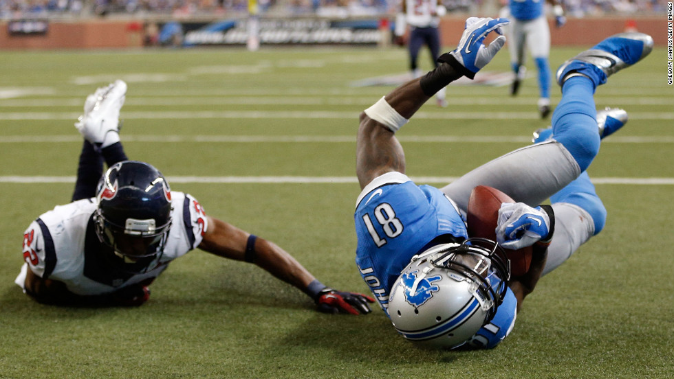 Calvin Johnson of the Detroit Lions makes a touchdown catch next to Alan Ball of the Houston Texans.