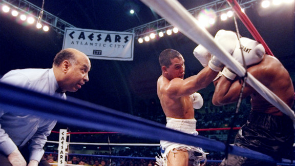 Camacho pins Sugar Ray Leonard to the ropes as referee Joe Cotez looks on during a bout in Atlantic City on March 1, 1997. Camacho won with a knockout in the fifth round, ending Leonard
