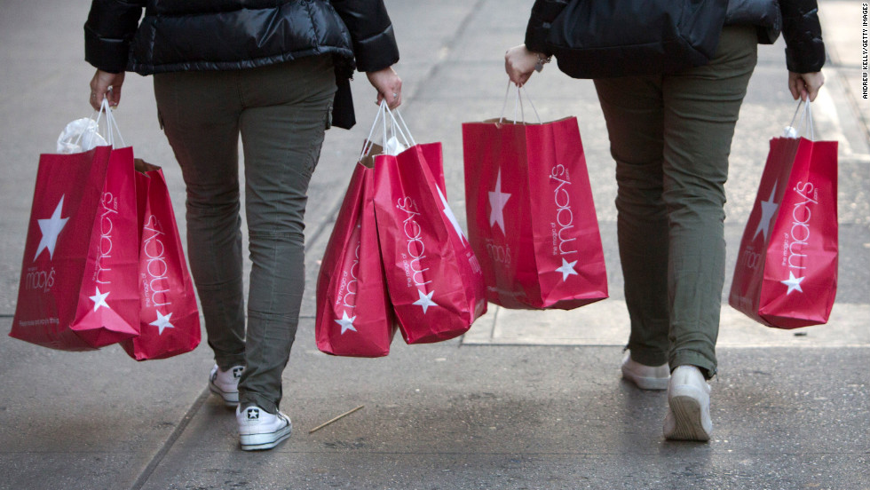 Women carry Macy's bags down 34th Street after shopping the Black Friday sales.