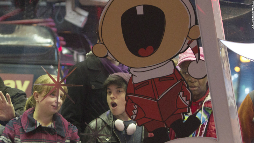 People peer inside the Toys R Us store before the Thanksgiving sale in New York's Times Square.