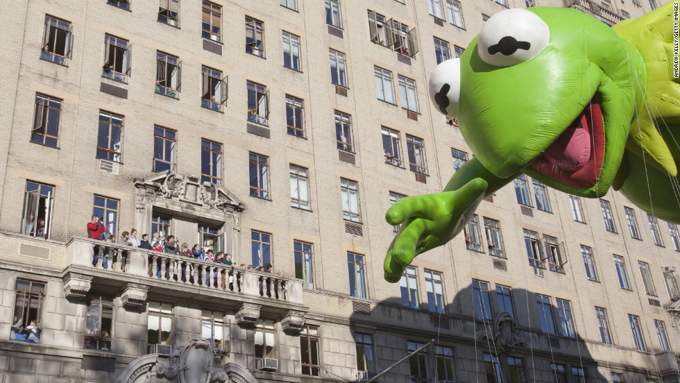 People watch the Kermit the Frog balloon make its way down Central Park West during the parade.