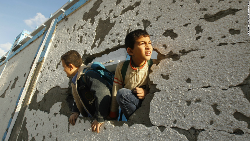 Palestinian schoolboys look through a hole at their damaged school in Gaza City on Saturday.