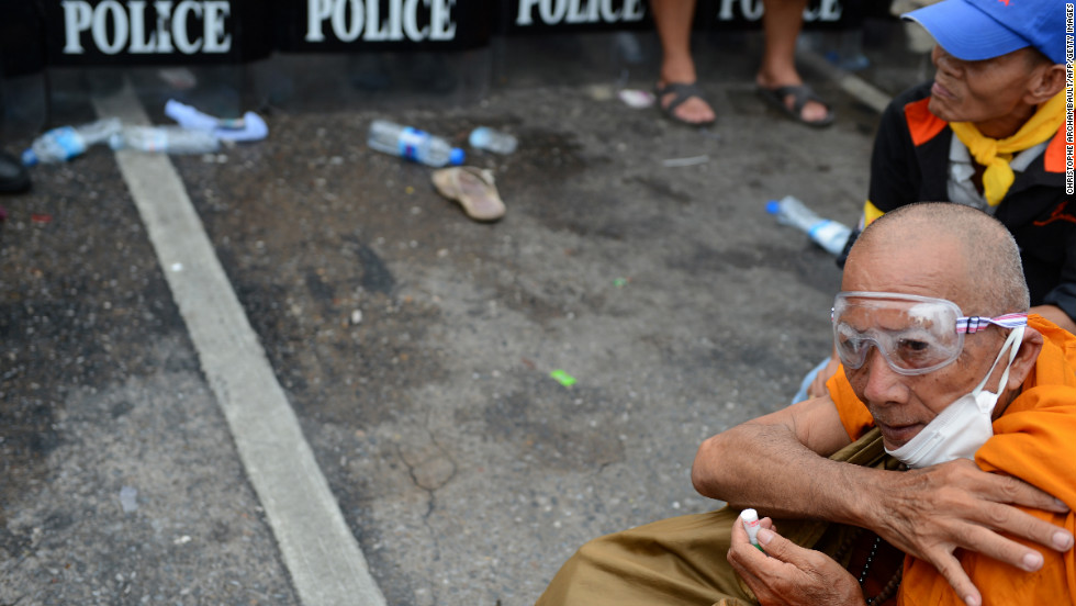 A Thai Buddhist monk sits in front of riot police officers as he takes part in the protest on Saturday.  Thai police fired tear gas and detained dozens of demonstrators as clashes erupted at the first major street protests against Prime Minister Yingluck Shinawatra's government.