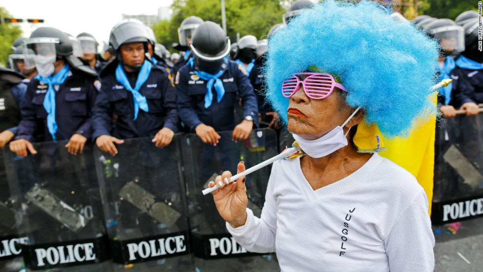 An anti-government protester walks past ranks of Thai riot police on Saturday.