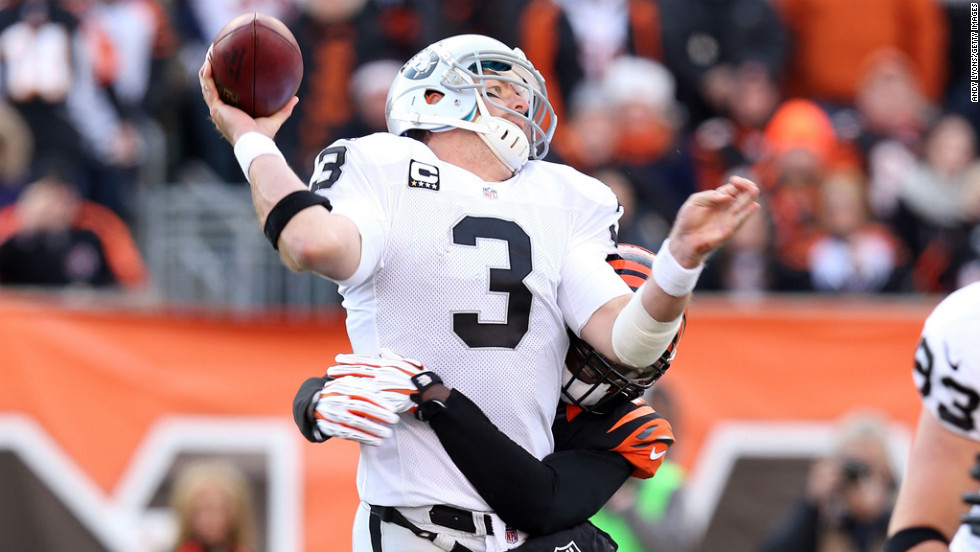 Carson Palmer of the Oakland Raiders is hit by Reggie Nelson of the Cincinnati Bengals as he throws a pass at Paul Brown Stadium on Sunday in Cincinnati.
