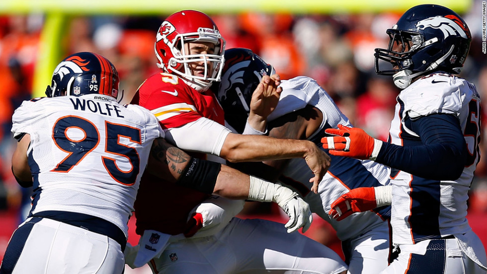Quarterback Brady Quinn of the Chiefs is hit by defensive end Derek Wolfe of the Broncos just after releasing the ball on Sunday.