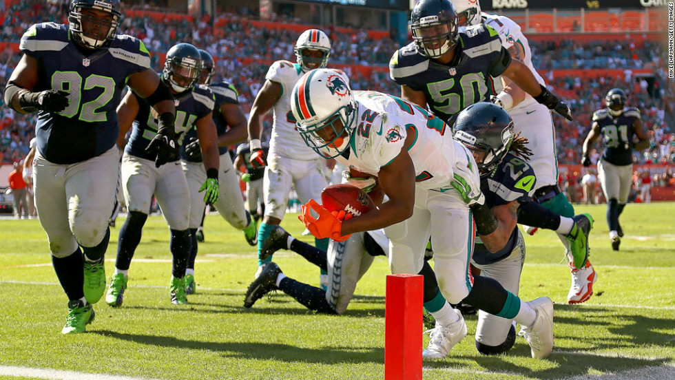 Reggie Bush of the Miami Dolphins rushes for a touchdown against the Seattle Seahawks at Sun Life Stadium on Sunday.