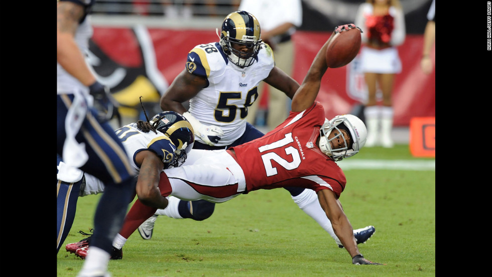 Andre Roberts of the Cardinals dives forward with the ball while being tackled by Janoris Jenkins of the Rams on Sunday.
