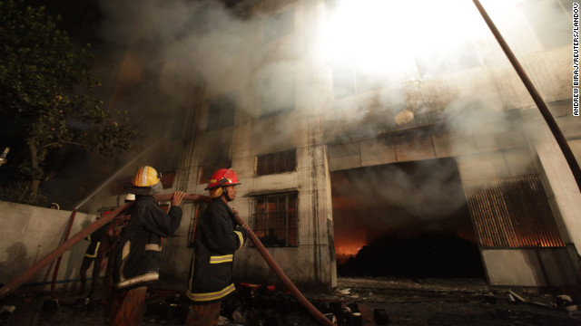 Firefighters work on the garment factory fire. An official said the fabric in the building was making the fire difficult to fight.
