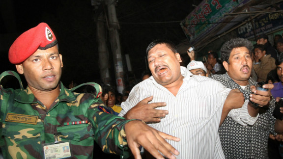 A man mourns on Saturday in Bangladesh as he is supported after his relative was killed in the flyover accident.