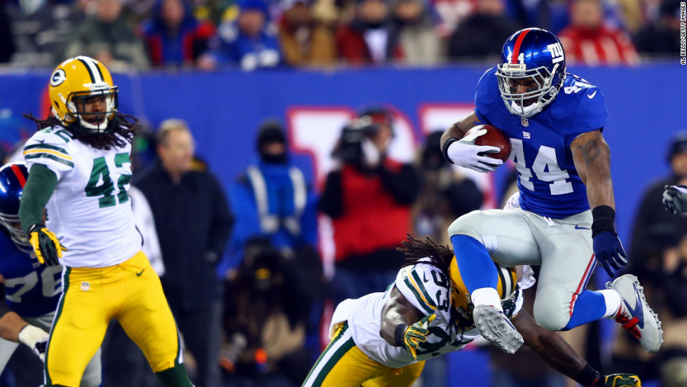 Ahmad Bradshaw of the New York Giants jumps over the attempted tackle of outside linebacker Erik Walden of the Green Bay Packers on Sunday, November 25, at MetLife Stadium in East Rutherford, New Jersey.