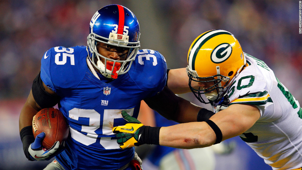 Andre Brown of the New York Giants tries to break a tackle by A.J. Hawk of the Green Bay Packers.