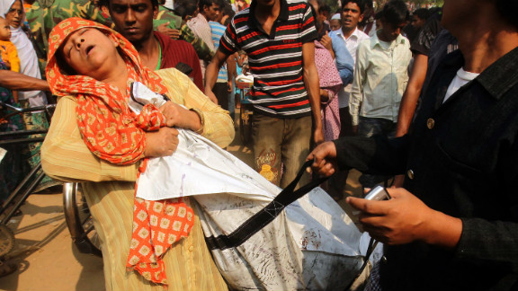 A woman mourns November 25 over the body of a relative who died in the fire.