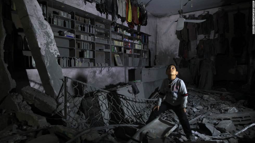 A boy stands in the rubble of a destroyed shop in Beit Lahia, in northern Gaza, on Monday, November 26.
