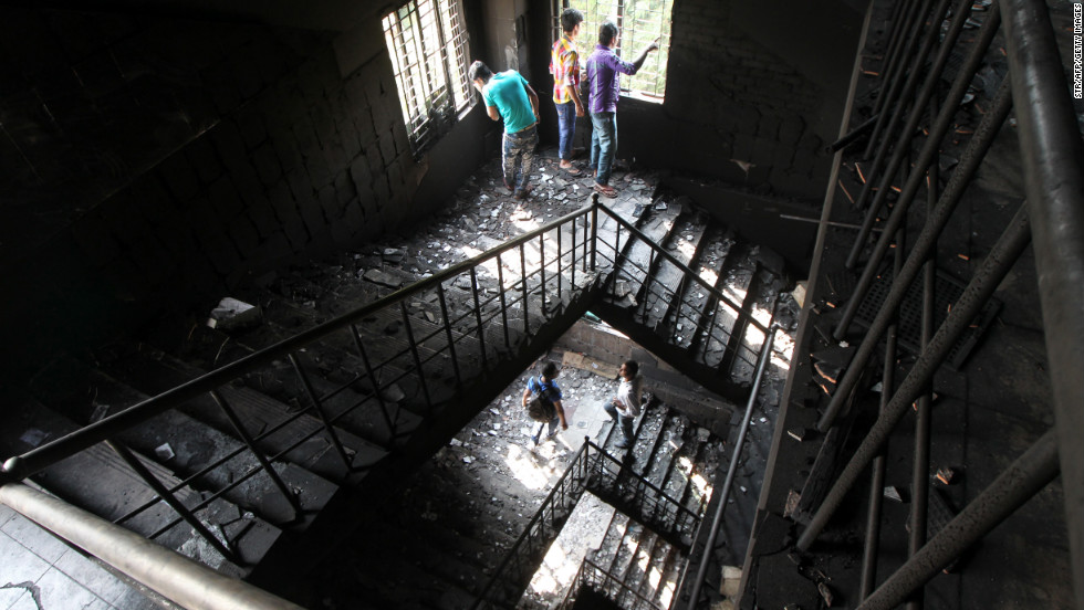 Bangladeshi garment workers check out the burned stairs of the plant on November 26.