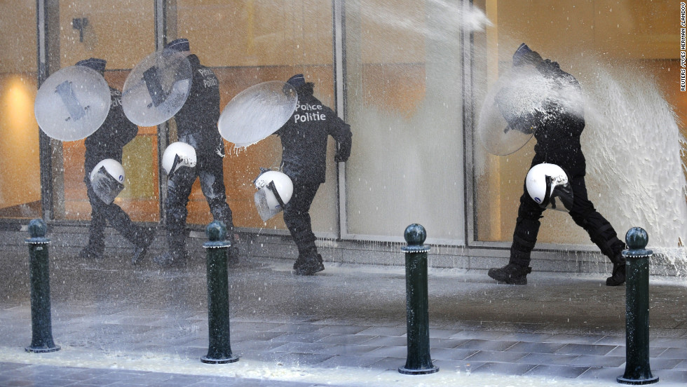 Police officers walk in front of the government building Monday, using shields to protect themselves from the milk.