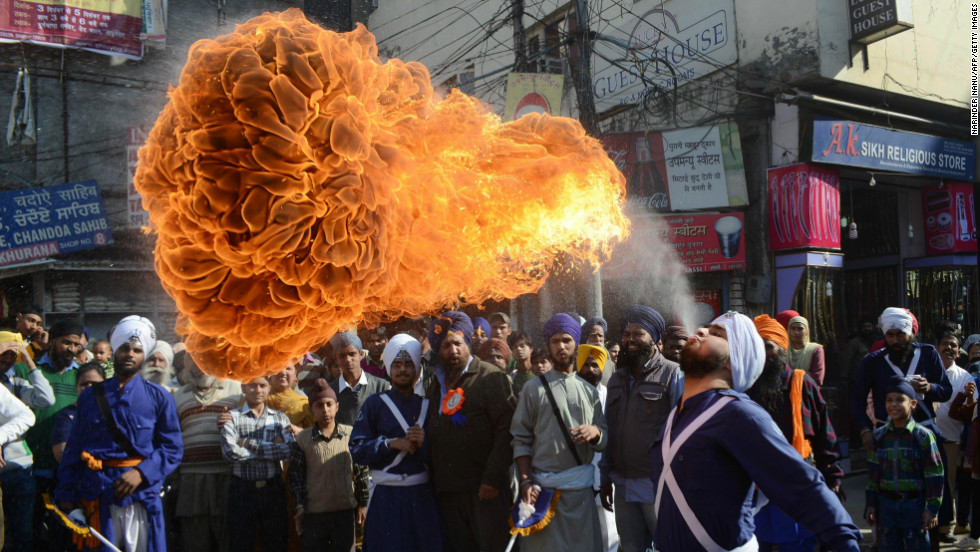 An Indian Sikh Nihang, or warrior, performs a fire-breathing act at a demonstration of gatka skills on Tuesday, November 27, during a procession from Sri Akal Takhat to the Golden Temple in Amritsar, India, the religion's spiritual center.