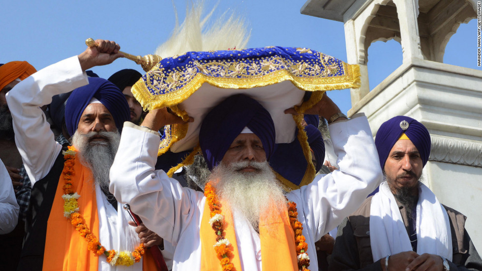 Indian Sikh head priests carry the Guru Granth Sahib, a Sikh holy book, during a procession at the Sikh Shrine Golden Temple in Amritsar on Tuesday, the eve of the 543rd birth anniversary of Guru Nanak Dev.