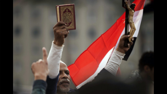 An Egyptian protester holds up a Quran and a figure of Christ on the cross during Tuesday