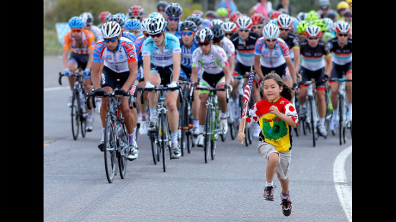 A young fan runs in front of the peloton during stage two of the USA Pro Challenge on August 21 in Sapinero, Colorado.