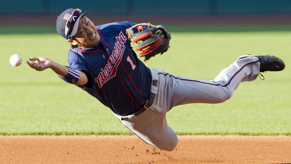 Second baseman Tsuyoshi Nishioka of the Minnesota Twins attempts to make a throw to first base during a game against the Cleveland Indians on August 6 in Cleveland, Ohio.