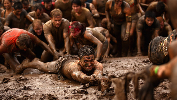 Competitors help pull each other up a mud hill during the 2012 Tough Mudder on April 1 in Phillip Island,  Australia.
