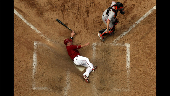 Aaron Hill of the Arizona Diamondbacks safely slides in to score a run past catcher Buster Posey of the San Francisco Giants at Chase Field on April 8 in Phoenix. The Diamondbacks defeated the Giants 7-6.