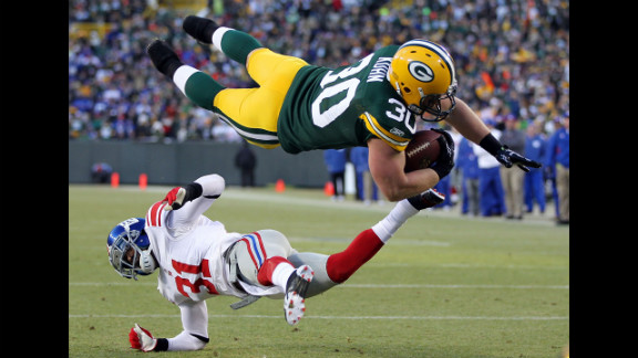 John Kuhn of the Green Bay Packers dives in for the touchdown over Aaron Ross of the New York Giants during their NFC divisional playoff game on January 15 at Lambeau Field in Green Bay, Wisconsin.