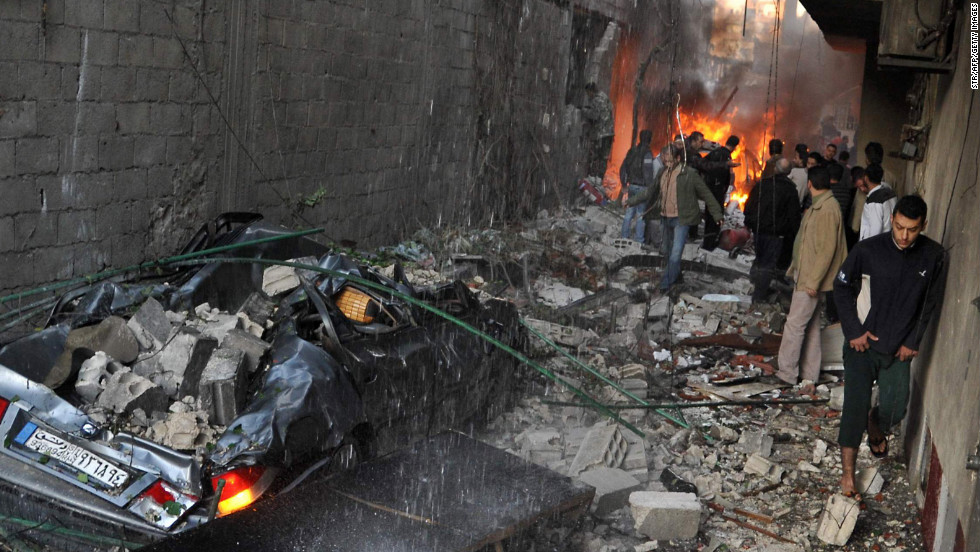 Syrian men inspect the scene of a car bomb explosion on Wednesday in Jaramana, a small town near Damascus that has provided a refuge for pro-government Syrians displaced in the civil war. Twin car bombs near the capital killed dozens, state media reported.