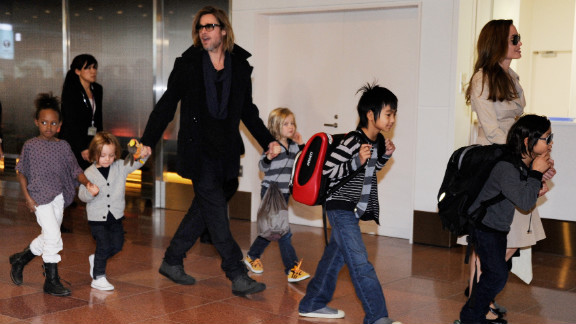 """Every so often, photographers will catch the entire Jolie-Pitt clan all at once, which is what happened here as the family arrives at the Haneda Airport in Tokyo in November 2011. They were in town to promote Pitt's film """"Moneyball,"""" which earned him another Oscar nomination, his third for acting."""
