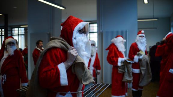 Men dressed as Santa Claus carry sacks through the meeting of volunteer Santa Clauses and angels on December 1 in Berlin.