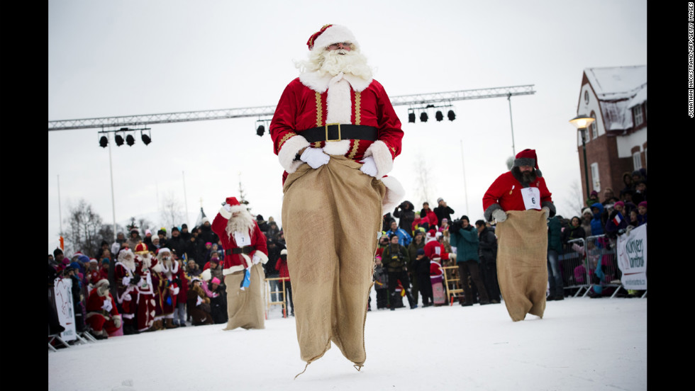 "Estonian Santa Claus ""Santa Aare,"" from left, Dutch Santa Claus ""Santa Holland"" and Swedish Santa Claus ""Snaretomten"" compete in the Kicksled Sack Race during the Santa Claus Winter Games in Gallivare, Sweden, on Saturday, November 17. Santas from around the world gathered to participate in Christmas-themed competitions that weekend."