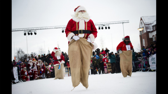 """Estonian Santa Claus """"Santa Aare,"""" from left, Dutch Santa Claus """"Santa Holland"""" and Swedish Santa Claus """"Snaretomten"""" compete in the Kicksled Sack Race during the Santa Claus Winter Games in Gallivare, Sweden, on Saturday, November 17. Santas from around the world gathered to participate in Christmas-themed competitions that weekend."""