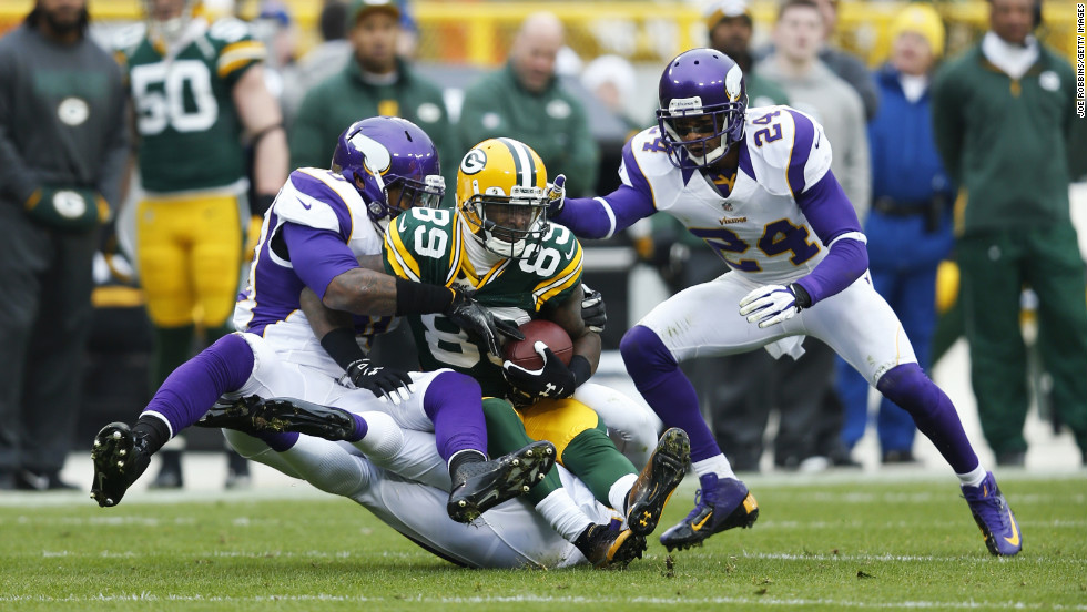 James Jones of the Green Bay Packers gets tackled on Sunday by Erin Henderson, left, and A.J. Jefferson of the Minnesota Vikings.