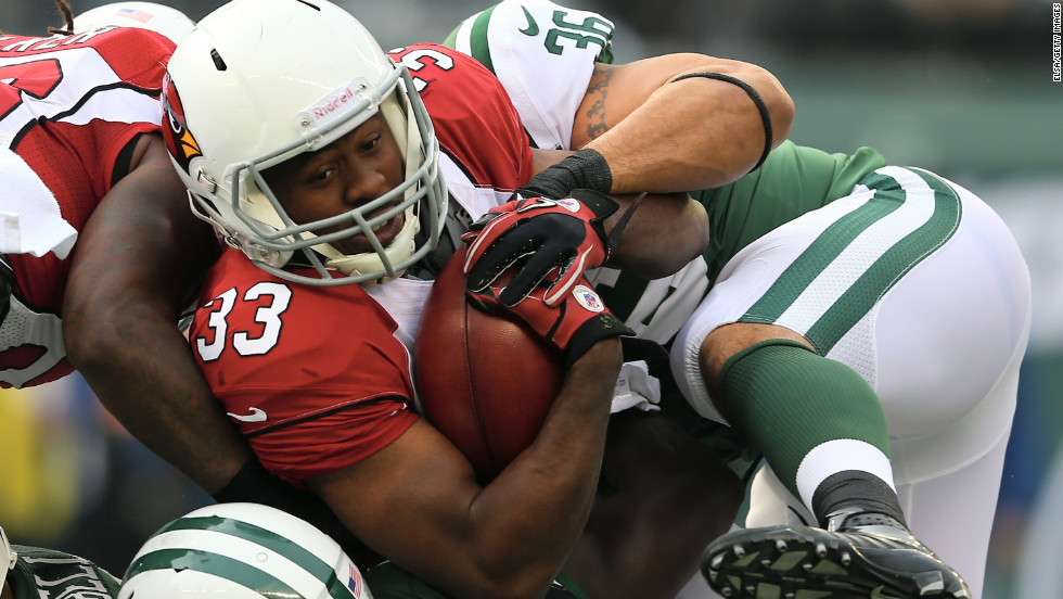 William Powell of the Arizona Cardinals is stopped by Lex Hilliard of the New York Jets in the first quarter on Sunday.
