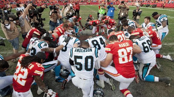 Players from the Kansas City Chiefs and Carolina Panthers gather at midfield for a prayer after the Chiefs
