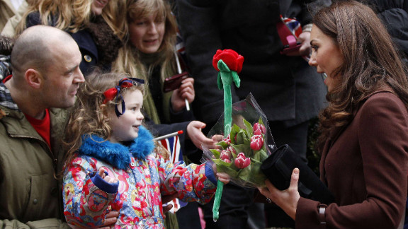 A young girl offers Catherine a toy rose as the Duchess visits Alder Hey Children